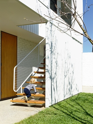 The open stair connects the studio with the backyard and encourages the use of the upper level.