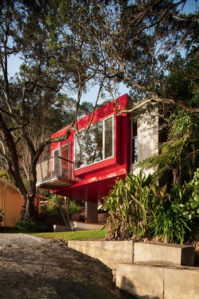 The vibrant shade of red not only references pohutukawa blossoms but also the traditional colour of the older baches.