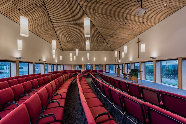 The worship hall features a dramatic timber ceiling and lantern-like lighting, hung low to create intimacy.