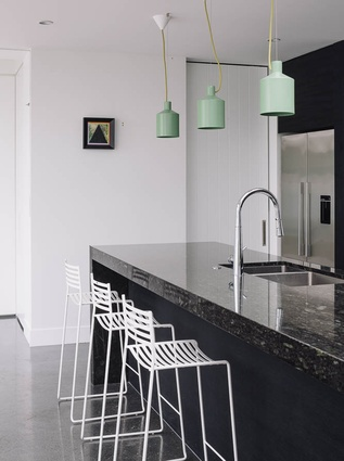 A bank of dark cabinetry surrounds the cooking centre and visually defines and anchors the kitchen space.