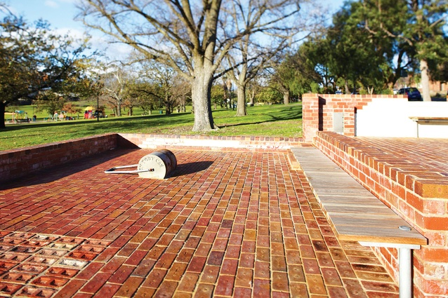 A steel tennis court roller is fixed into the brick paving – a reminder of the site's former life.