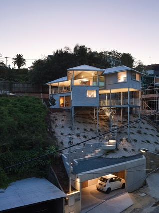 The house is propped on stilts, sited on a steep, south-east-facing slope in Hamilton, Brisbane.