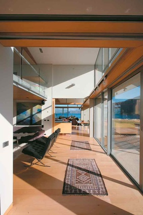 Looking through to the kitchen and dining area of this Wanaka house, from the lounge with mezzanine space above, designed by John McCoy.