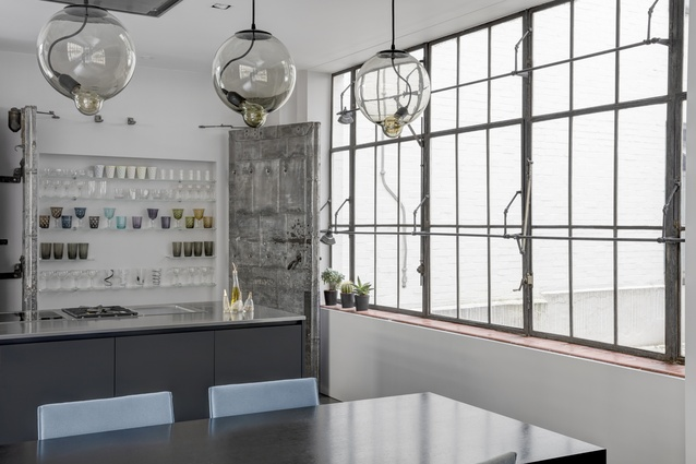 In the kitchen, a pair of steel-strapped vault doors celebrate the building's heritage and conceal a compact cupboard.