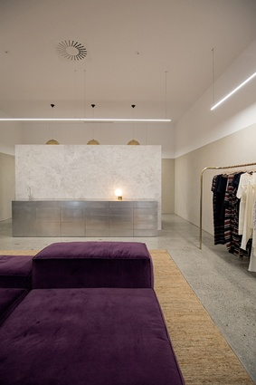 A plush purple sofa anchors the space with a note of softness and femininity.