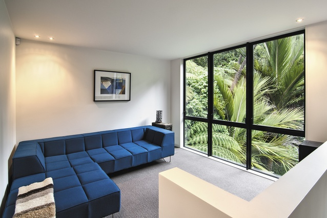 The sitting room enjoys green views through the floor-to-ceiling glazing.
