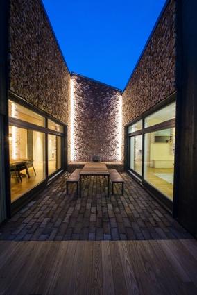 A small, sheltered courtyard that can be used for outside dining in moderate weather is  surrounded by walls made of stacked firewood and brick.