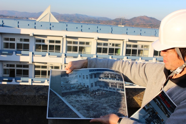 Our guide holds a photo of surging water taken from the high school roof on the day of the 2011 tsunami.