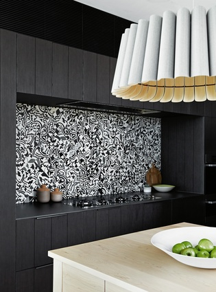 The cooking area is backed by a playful mosaic splashback.