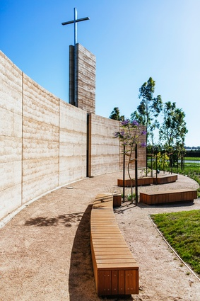 Behind the curved rammed earth wall to the north is a quiet reflection space. Vertical openings in the wall offer glimpses into the chapel.