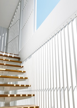 The white battened facade of the studio peels away from the building walls to allow for an open stair.
