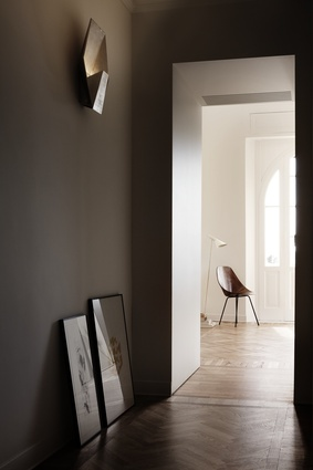 Hallway with parquet flooring in herringbone pattern. Leather chair and wall sconces lend a historic, almost gladiatorial, element to the interior.