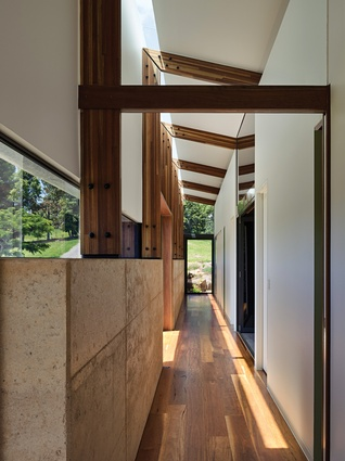 Slots of sashless glazing sit between the rammed earth wall and the folded roof line; sections of the wall push out into day beds or small porches.