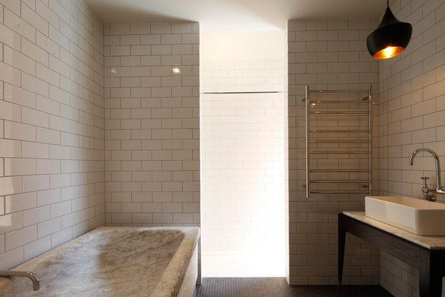 The bathroom combines the solid elegance of marble with contemporary tiling.