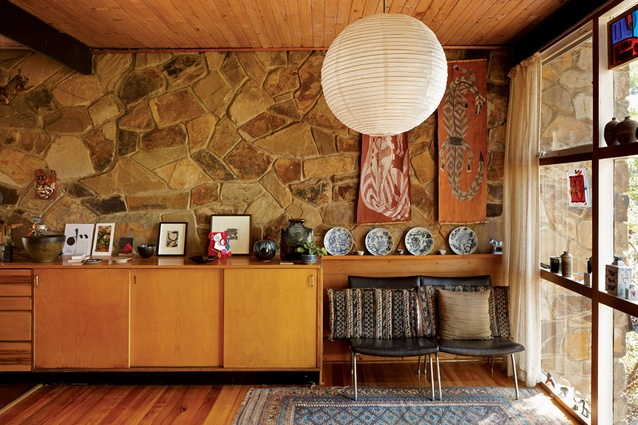The western wall is faced in rough local stone, lending thermal mass and a dramatic backdrop to the kitchen and living area.