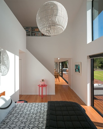 The master bedroom with stairs leading to the mezzanine space at the far end.