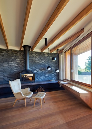 A dark brick wall behind the wood fireplace in the living room is a stunning focal point, but also works to store heat.