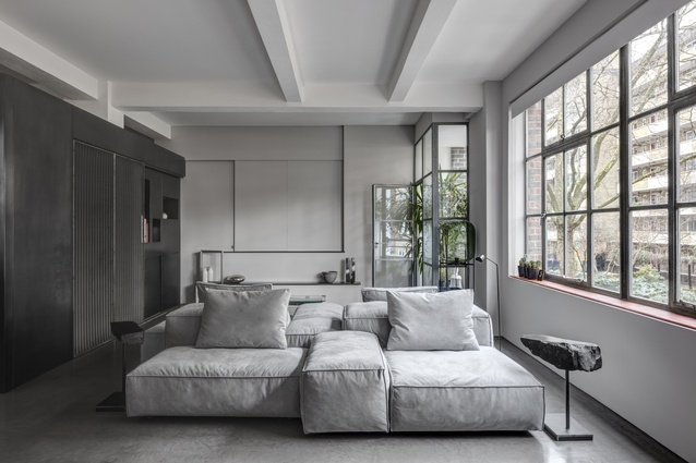The pared-back colour palette layers greys, whites and metallics. A generously scaled sofa takes centre stage.
