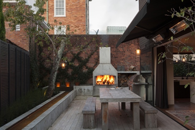 The dining room of the new house opens on to a courtyard with an outdoor fireplace.
