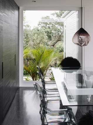 A glass-topped table and acrylic chairs recede from view, allowing the greenery to come to the fore.