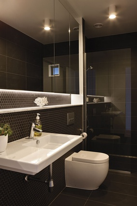 The dark and elegant bathroom with masses of storage hidden behind the mirror cabinet.