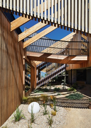 The pavilions are stitched together by pergola beams, a walkway to the roof deck and an enclosed staircase, creating layers of diagonal lines.