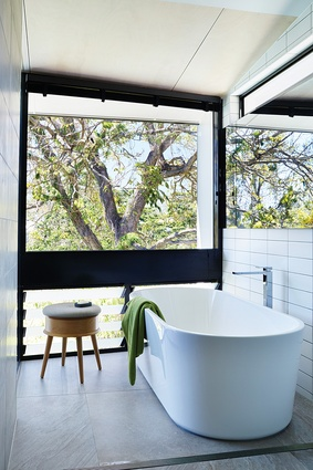 A low bank of louvres in the main ensuite allows for ventilation, while fixed glazing above frames the treetop view.