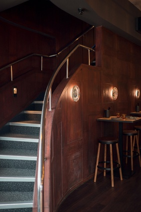 A gently-curving staircase leads to the upstairs level. Seating is casual in nature and raised to overlook the street.
