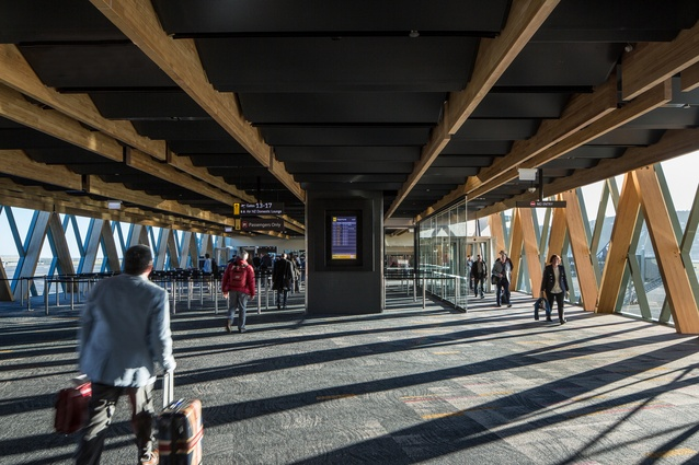 The Wellington Airport South West Pier link extension features a folded perforated metal ceiling panel system and timber façade structure that provides a sense of warmth.