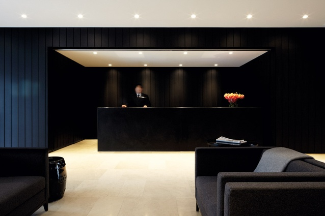 Black wall panels contrast with white limestone flooring in reception.
