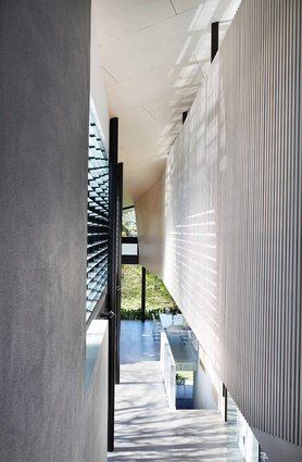 At entry, the eye is drawn along a kinked corridor to the living area, past the garden courtyard that draws in further light.