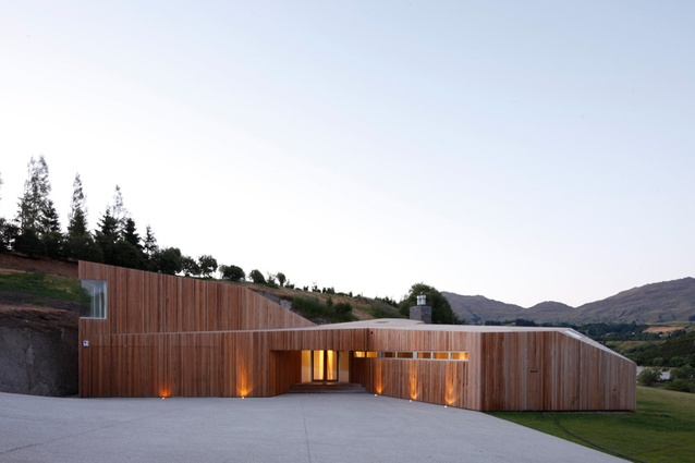 The cedar skin seamlessly envelops the entire form, making walls and roof read as a single, unified object.