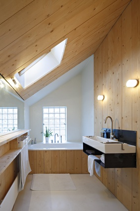 The timber-finished bathroom glows with natural light.