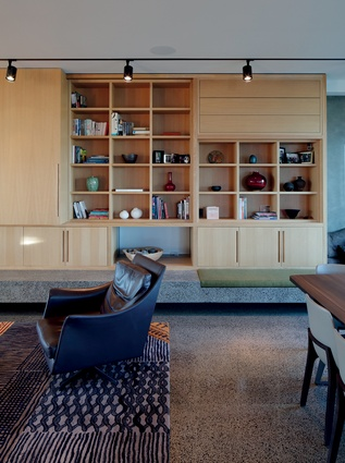 The expansive shelving and storage cabinets extend along a main wall and incorporate a fireplace.