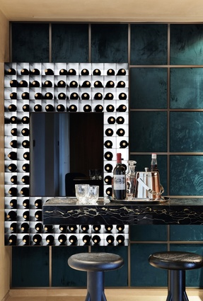 The minibar features a blue velvet fabric and metal grid backdrop and metal wine shelves painted black with electrostatic paint.