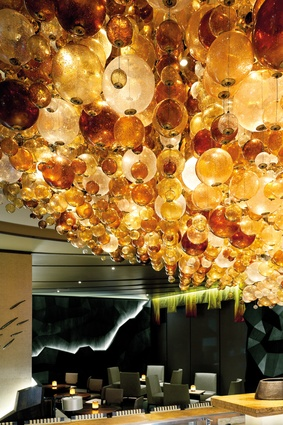 Hand-blown glass orbs hang in clusters providing a series of centrepieces through the space.
