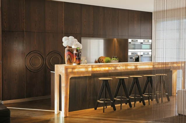 The kitchen – with Miele appliances, Gessi tap  and Tom Dixon stools – has been designed like  a piece of cabinetry since it is so prominent in the living space.