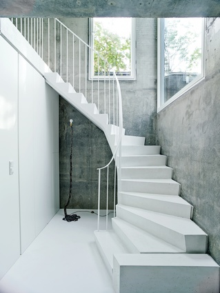 The white concrete stairs add a sculptural element to the overall scheme, complemented by a floor lamp by artist Franz West.