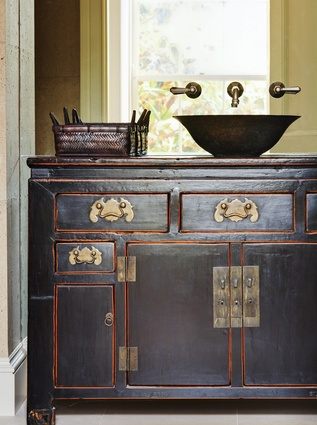 A black-lacquered Chinese cabinet is used as a bathroom vanity.
