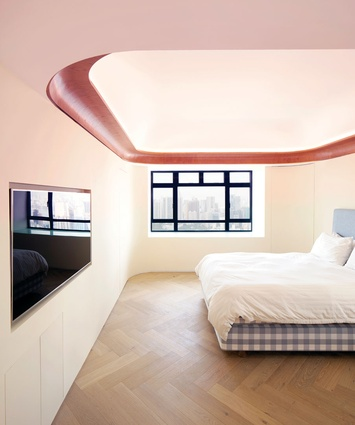 The timber perimeter of the bedroom ceiling conceals existing concrete beams and LED lighting.
