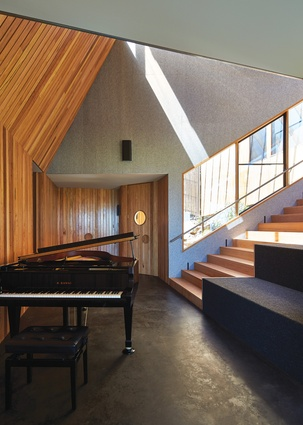 The stair is not only a bridge between the home's two halves, it's also an amphitheatre to witness piano performances.