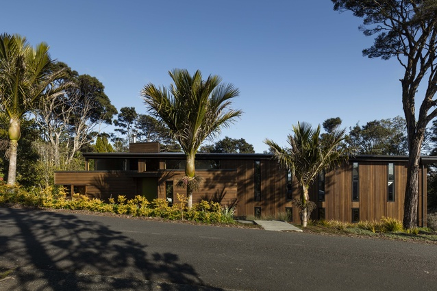Tawini House, Titirangi. The house is built on a steep site and gives away little to the street, with vertical windows that allows glimpses in or out.