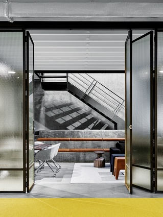 On the ground floor, folding glass doors separate the working zone from an open play space.