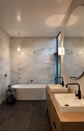 The bathroom features marble, wood and black tapware. A giant circular mirror makes the space appear larger.