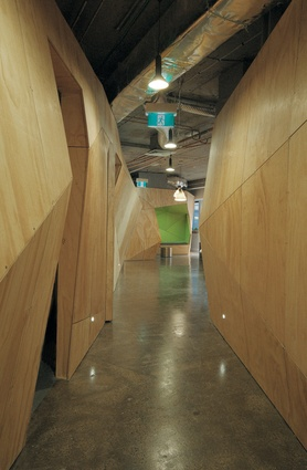 The triangulated plywood walls symbolize abstracted tree trunks, bringing nature indoors.