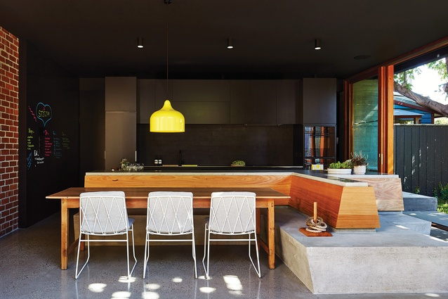A concrete kitchen bench folds down to become built-in seating that continues to the threshold of the extended living room and garden.