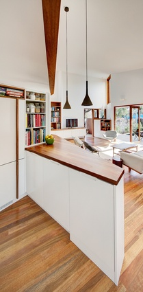 The flat ceiling over the kitchen benchtop rises to a much higher vaulted ceiling over the living space.