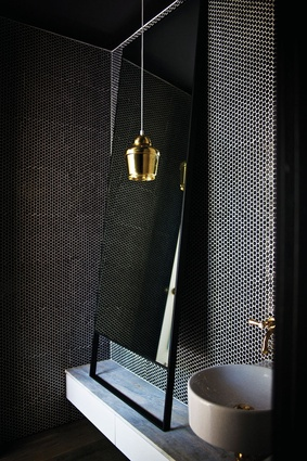 The powder room features dark penny-round tiles, a gold pendant light and a steel-rimmed mirror.