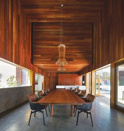 A void above the dining room is clad in dark timber to emphasize the mood of this space.