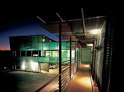 Looking along the entry ramp towards the entry verandah on the south elevation. The building is organized as two intersecting boxes, with undercroft carpark and service space.Image: Scott Burrows